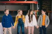 Fotografia Brillantemente vestito gruppo di bambini che tengono le mani e guardando laltro