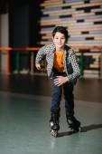 Fotografie Selektivní fokus roztomilý usměvavý chlapec Bruslení na válečky