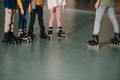 Photo Partial view of children in roller skates listening to trainer instructions