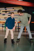 Photo Handsome young trainer giving skating instructions to smiling boy