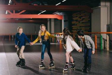 Smiling children in roller skating on roller rink and holding hands