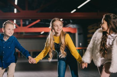 Selective focus of smiling beautiful children holding hands while moving on roller rink