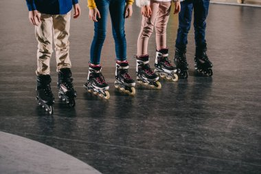 Partial view of children legs in roller skates standing in roller rink