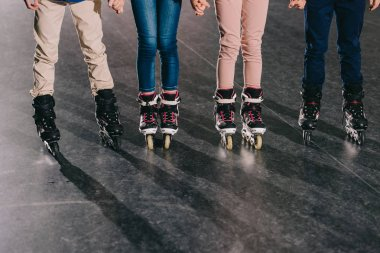 Partial view of children in roller skates standing in roller rink and holding hands