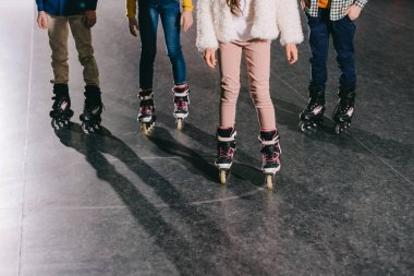 Cropped view of children in roller skates standing in roller rink
