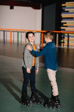 Pretty boy touching laughing friend while standing in spacious roller rink
