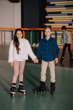 Two beautiful smiling children in roller skates standing with holding hands