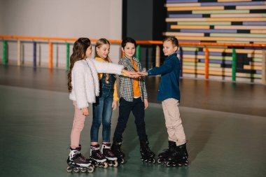 Smiling children in roller skates staying on roller rink and stretching hands together