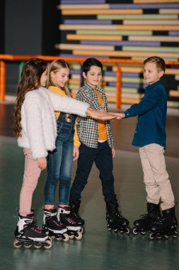 Selective focus of pretty smiling children in roller skates stretching hands together