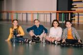 Fotografie Fröhliche Kinder in Rollschuhe sitzen auf Boden