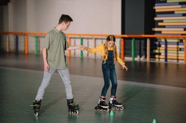 Handsome instructor holding children hand while explaining skating technics