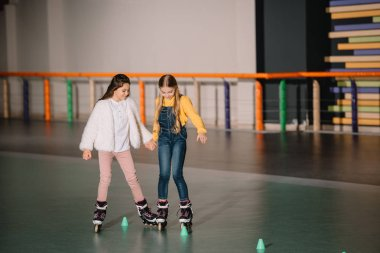 Beautiful kids practicing rolling skating while holding hands