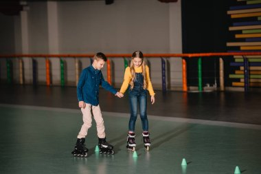Two children practicing scating on rollers with holding hands