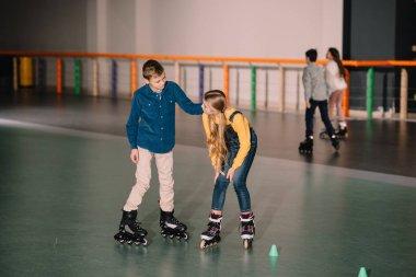 Joyful kids practicing roller skating on rink together