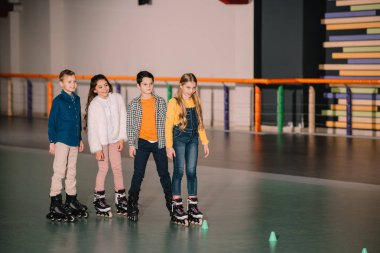Smiling cute kids ride roller skaters together