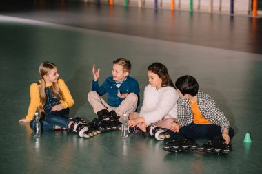 Kids in roller skates smiling and talking around