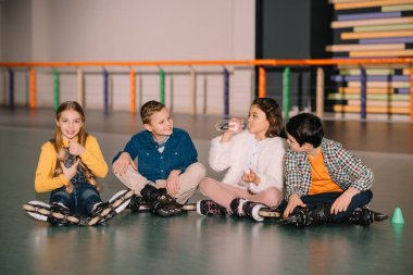 Children in roller skates drinking water on skating rink