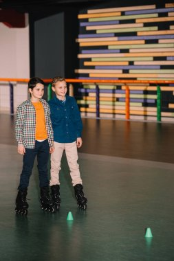 Little brothers in roller skates posing with smile