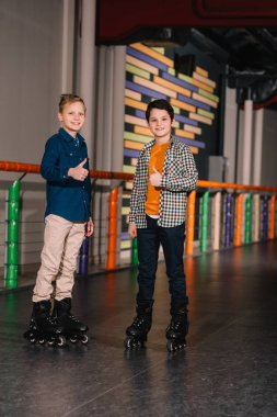 Preteen boys in roller skates posing with thumbs up
