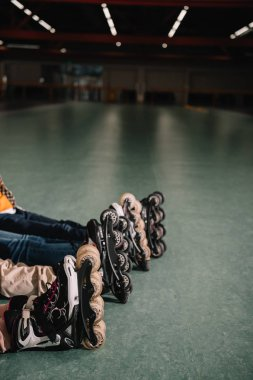 Partial view of children in roller skates resting together