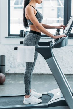 cropped shot of young sporty african american woman exercising on treadmill in gym