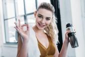 Fotografia ragazza sportiva felice che tiene la bottiglia di sport e che mostra segno giusto in palestra