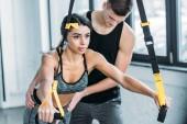 mužské školitel pomáhá mladé afroamerické ženy cvičení s Cadillac v tělocvičně