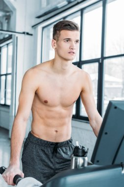 muscular shirtless man running on treadmill and looking away in gym