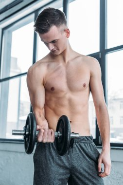 muscular shirtless man exercising with dumbbell and looking at biceps in gym