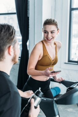 smiling sporty girl running on treadmill and looking at young man on foreground in gym