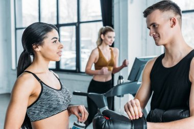 Sportive young man and woman talking and looking at each other in gym, sportswoman training on treadmill behind stock vector