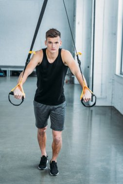 full length view of handsome muscular young man exercising with resistance bands and looking at camera in gym