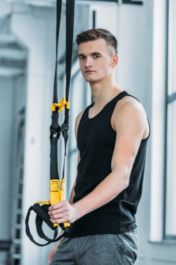 handsome athletic man standing with resistance bands and looking at camera in gym