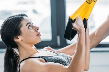 young african american woman training with suspension straps in gym
