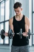 koncentrované svalnatý muž trénink s činkami v posilovně