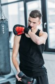 athletic young sportsman wearing boxing glove with teeth in gym