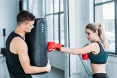 male trainer holding punching bag and smiling girl in boxing gloves training in gym