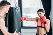 Fotografia allenatore maschio che tiene sacchetto di perforazione e ragazza dellafroamericano in guantoni da Boxe allenamento in palestra