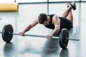 sportos yougn ember feküdt, és a súlyzó a tornaterem képzés