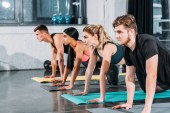 Photo multiethnic athletic young men and women exercising on yoga mats and looking away in gym