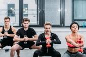 sportovní mladých mužů a žen dělá sit ups s činkami v posilovně
