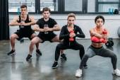 Fotografie sportovní mladých mužů a žen, cvičení s činkami a při pohledu na fotoaparát v tělocvičně