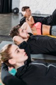 Photo sporty young multiracial people lying on yoga mats and doing abs in gym
