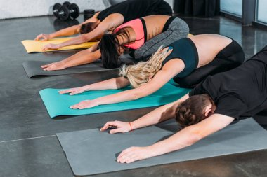 sportive young friends stretching and training on yoga mats in gym