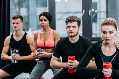 athletic young multiethnic men and women doing sit ups with dumbbells in gym