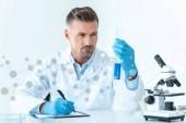 Fotografia Bello scienziato che esamina la provetta con il reagente blu