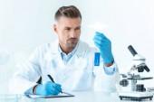hezký vědec s modrým činidel při pohledu na zkumavky
