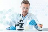 Fotografia fuoco selettivo del bello scienziato in protettiva occhiali che fa esperimento con microscopio isolato su bianco con simboli medici