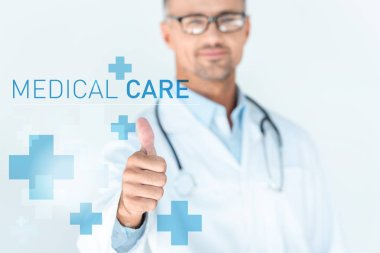 selective focus of handsome doctor in glasses with stethoscope on shoulders showing thumb up with medical care lettering