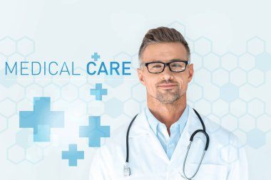 handsome doctor in glasses with stethoscope on shoulders looking at camera with medical care lettering